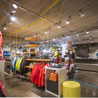 Sports shop with various displays such as jackets and shirts. Concrete ceiling and floor.