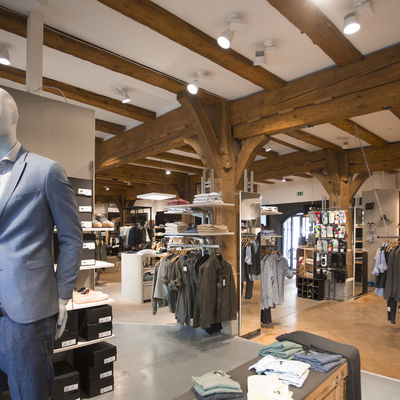 Chic fashion store from the inside, with beams on the ceiling and wooden support beams.