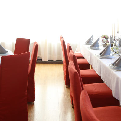 Elegant and festive tables around which red chairs stand.