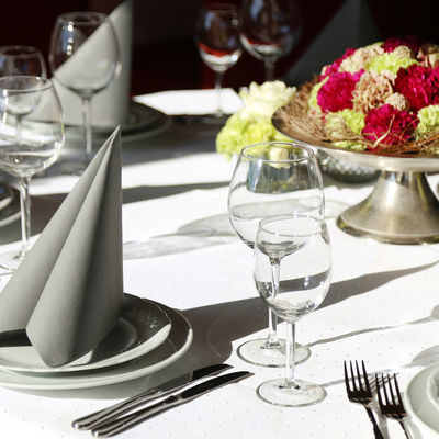 Elegantly laid table with gray napkin, wine and water glasses and floral decorations in the middle.