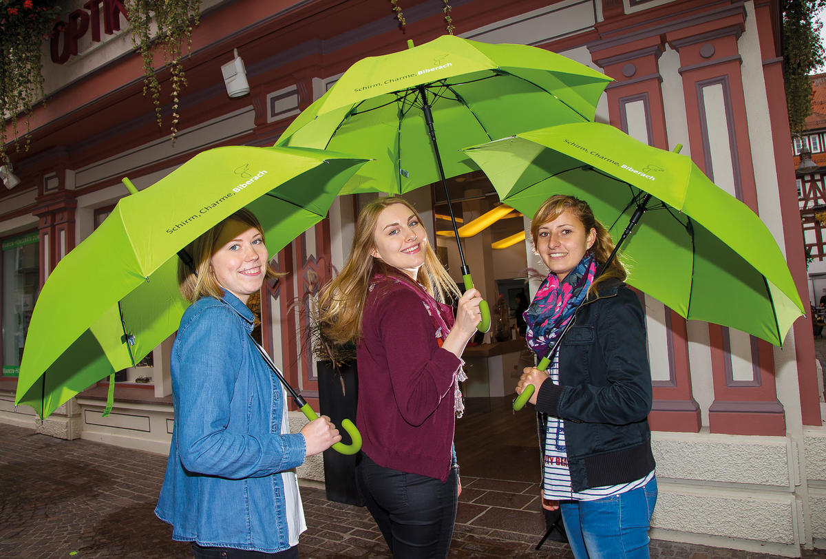 Three young women with green umbrellas in hand are looking at the camera with a smile. The rental umbrella is available for 10 euros at the tourist information in the town hall.